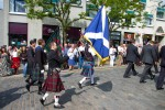 Bekilted persons bearing flag